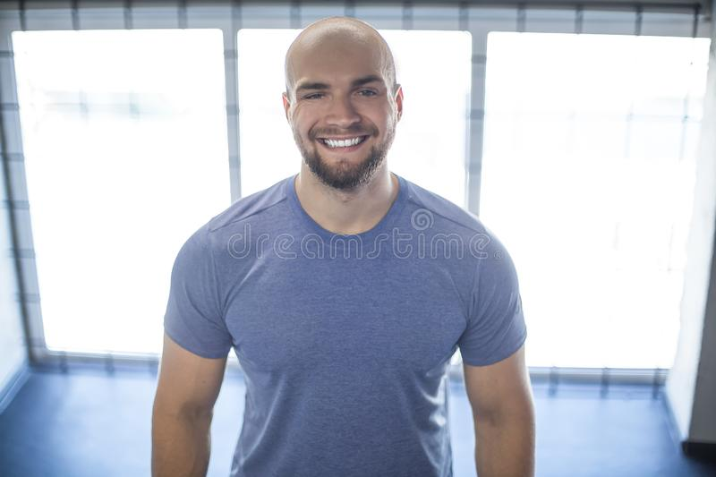 Portrait of a young smiling athlete in the gym. stands on the background of beautiful windows. workout was successful stock images