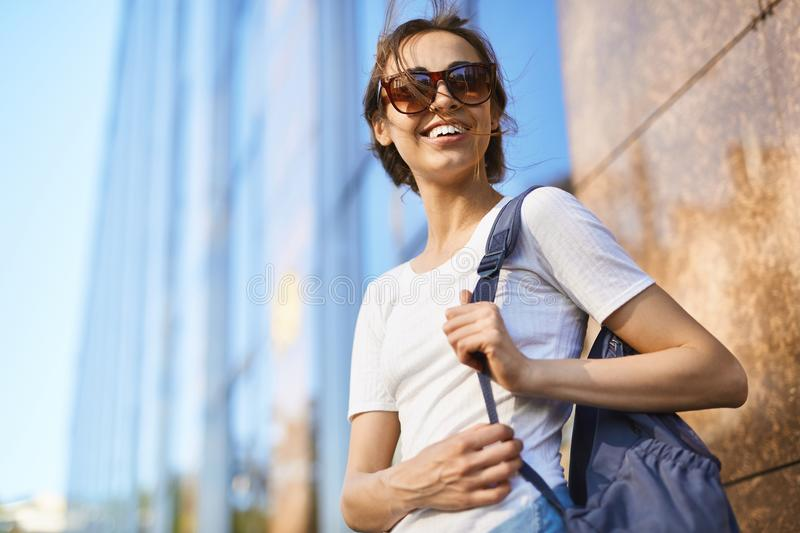 Portrait of a young attractive woman walking city at sunny day royalty free stock images