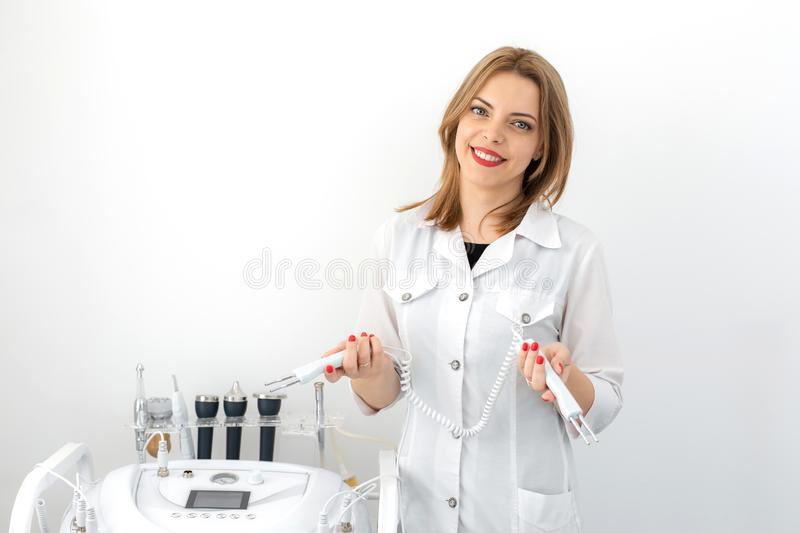 Portrait of a young smiling beautiful girl of a professional beautician at the workplace in a white clean office stock photo