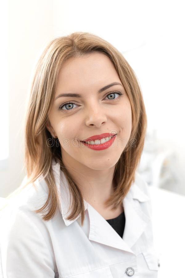 Portrait of a young smiling beautiful girl of a professional beautician at the workplace in a white clean office stock images