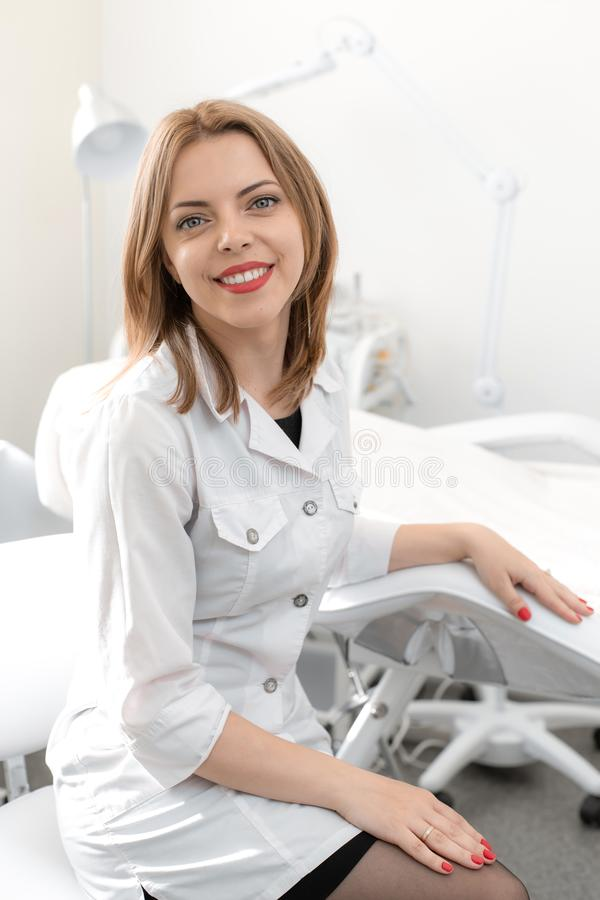 Portrait of a young smiling beautiful girl of a professional beautician at the workplace in a white clean office royalty free stock images