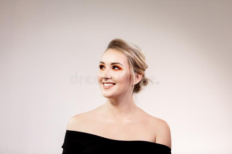 Portrait of young smiling blonde woman with professional makeup stock image
