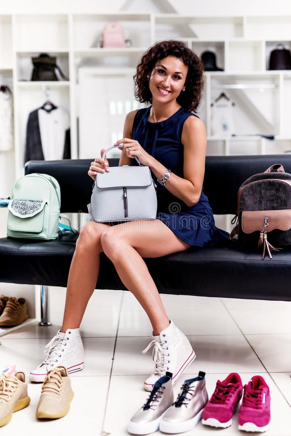 Portrait of young smiling brunette picking a new handbag while sitting on a bench looking at camera in clothing store. Portrait of young smiling brunette stock photos
