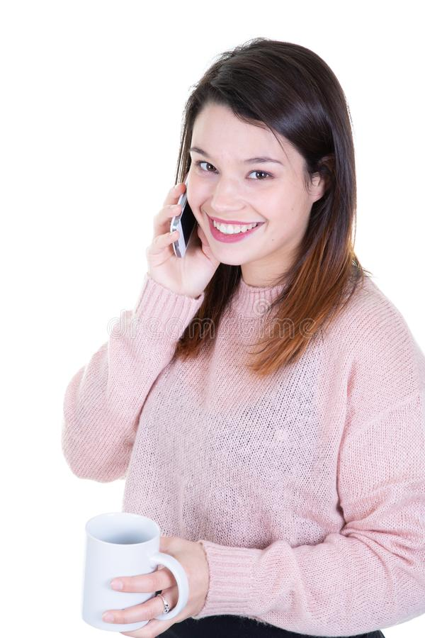 Portrait of young smiling brunette woman with mobile phone looking side stock photo
