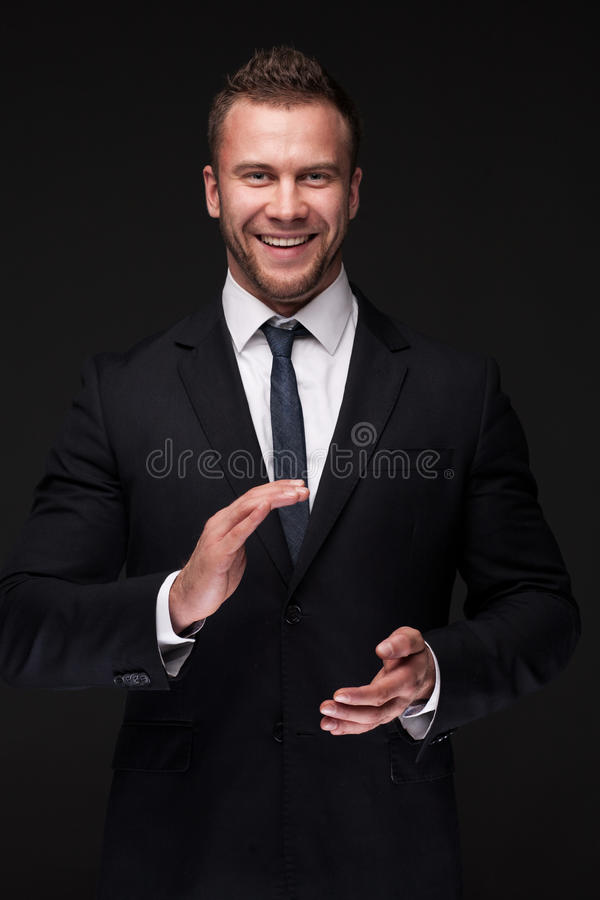 Portrait of young smiling businessman. Applauding. isolated on dark background stock photography
