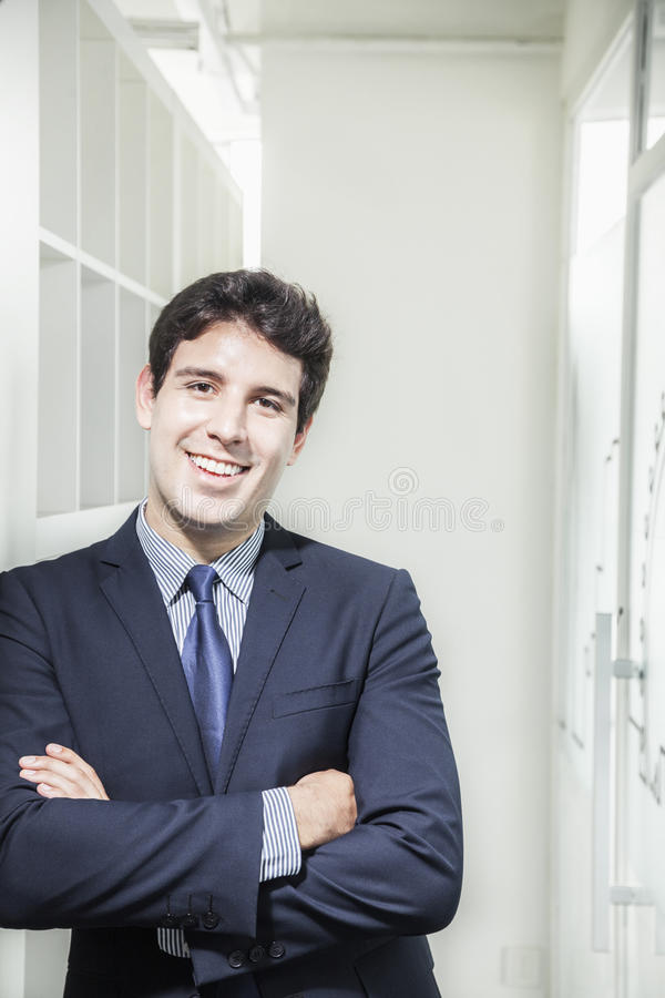 Portrait of young smiling businessman with arms crossed and looking into the camera stock photo