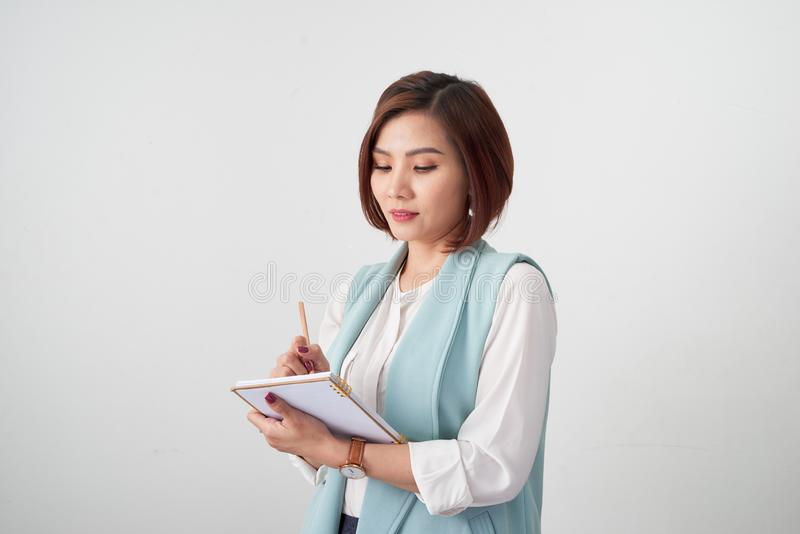 Portrait of young smiling businesswoman in the office, holding documents on light background royalty free stock photo