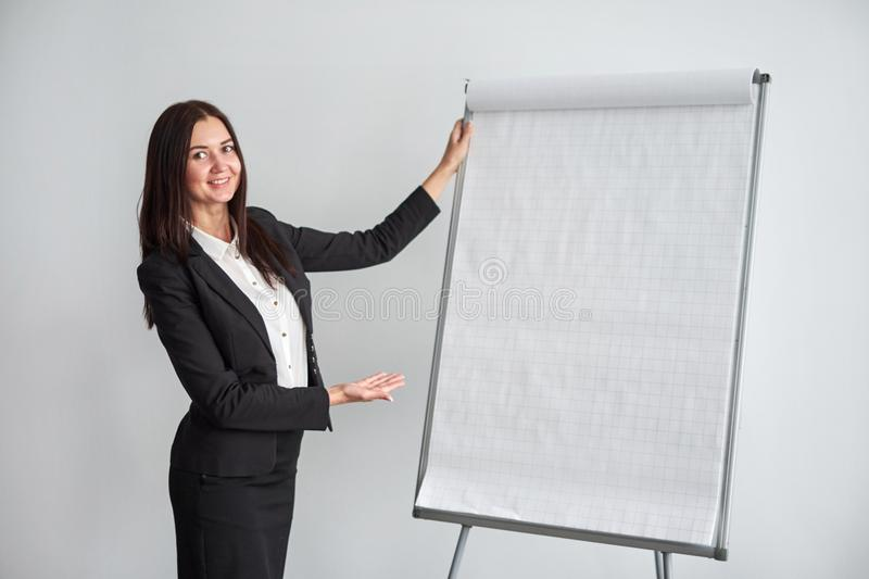 Portrait of young smiling businesswoman standing by flipchart in office stock image