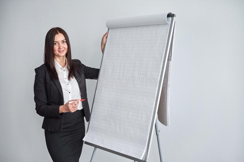 Portrait of young smiling businesswoman standing by flipchart in office stock photo