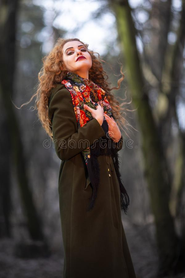 Portrait of Young Smiling Caucasian Female With Red Hair Posing in Forest Outdoors royalty free stock image