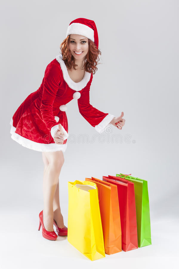 Portrait of Young Smiling Caucasian Ginger Santa Helper Girl with Colorful Shopping Bags stock photo