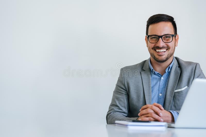 Portrait of young smiling cheerful businessman in office looking at camera copy space stock image