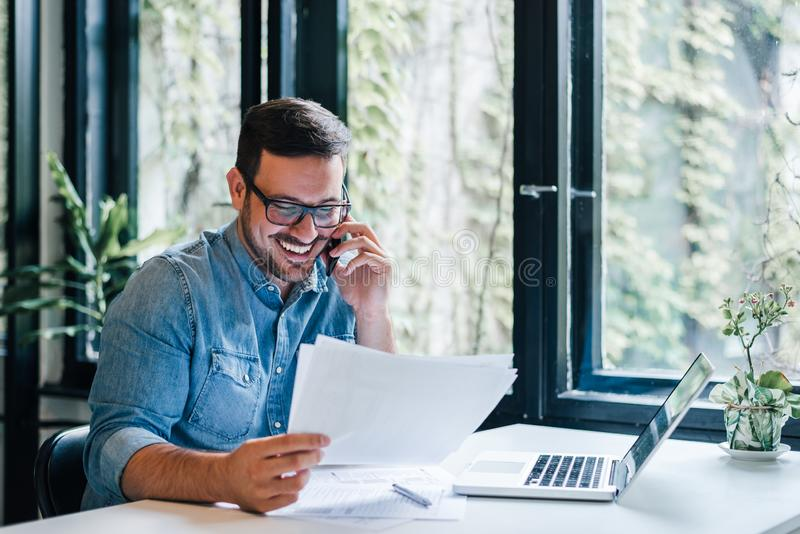 Portrait of young smiling cheerful entrepreneur in casual office making phone call while working with charts and graphs looking at royalty free stock photo