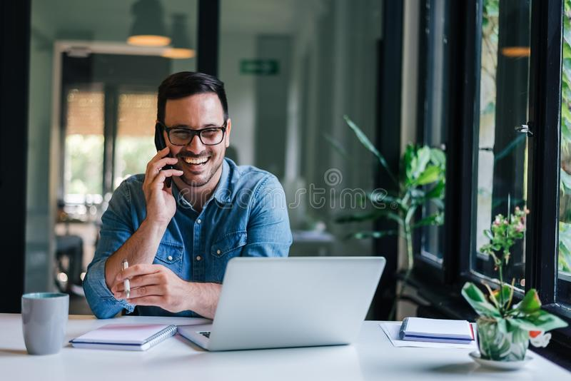 Portrait of young smiling cheerful entrepreneur in casual office making phone call while working with laptop stock images