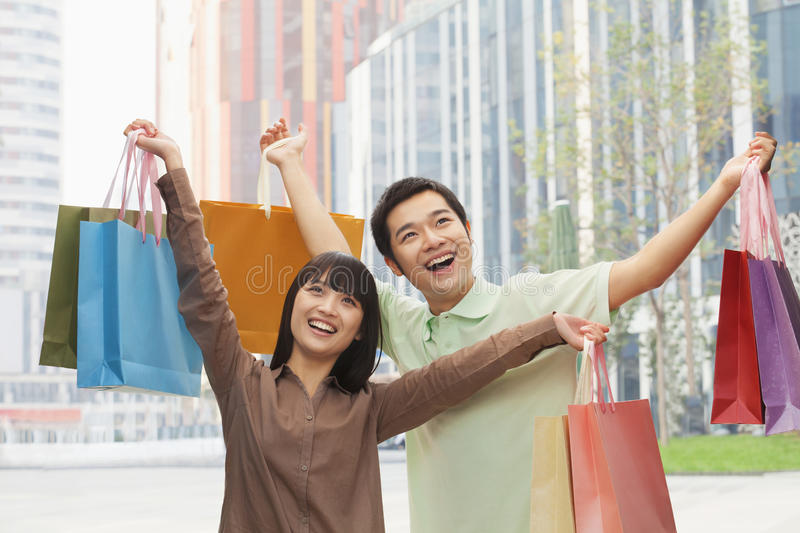 Download Portrait Of Young, Smiling Couple Going Shopping And Holding Colorful Shopping Bags On The Street, Outdoors In Beijing, China Stock Image - Image: 31106215