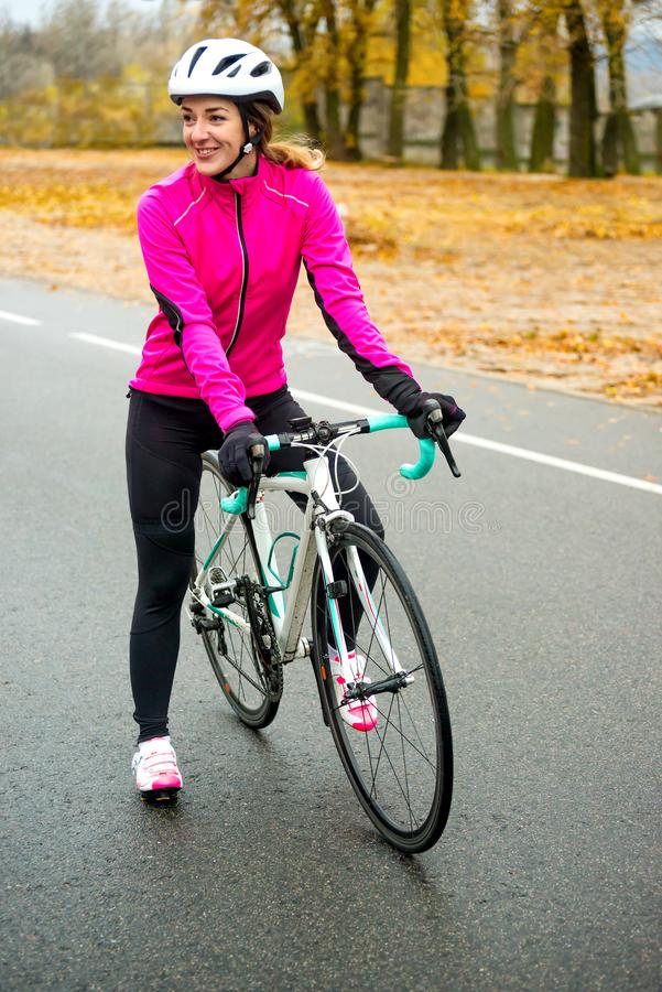 Portrait of Young Smiling Female Cyclist in Pink Jacket Resting with Road Bicycle in the Cold Sunny Autumn Day. Portrait of Young Smiling Female Cyclist in stock photography