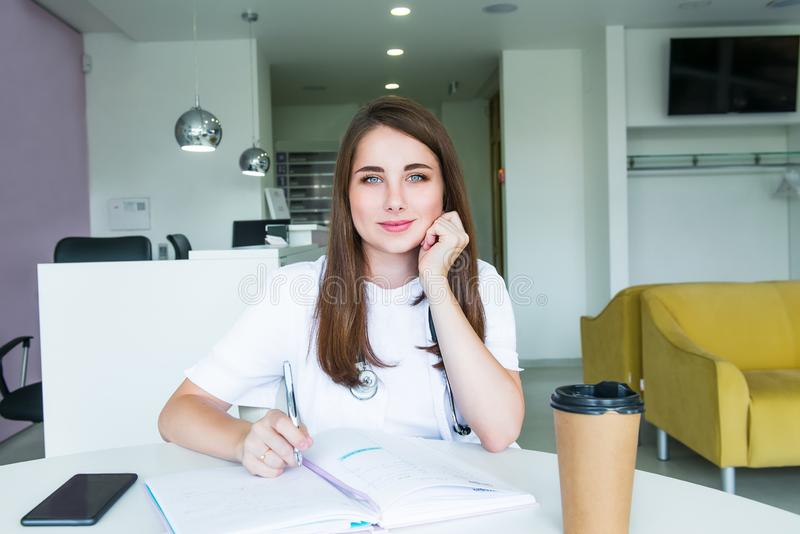 Portrait of young smiling female doctor making notes in notebook while sitting behind the table with phone and coffee inside of stock images