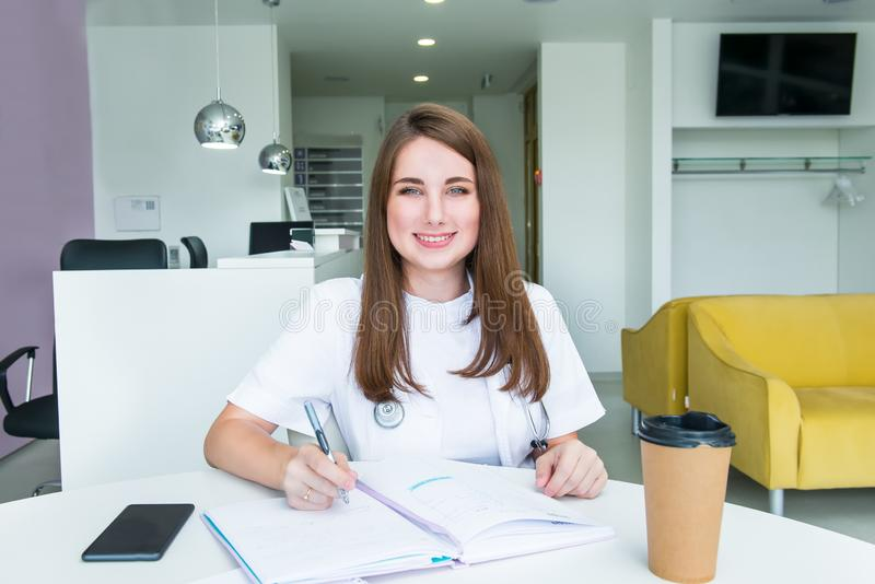 Portrait of young smiling female doctor making notes in notebook while sitting behind the table with phone and coffee inside of stock image