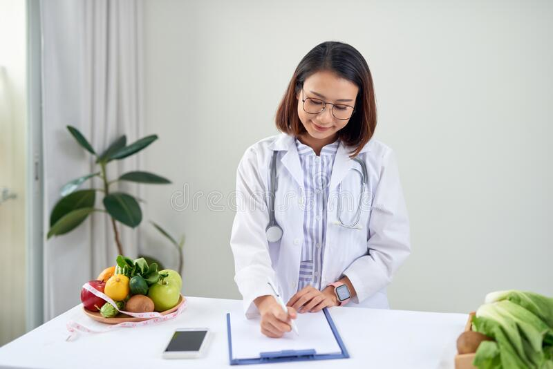 Portrait of young smiling female nutritionist in the consultation room. Dietitian working on diet plan royalty free stock image