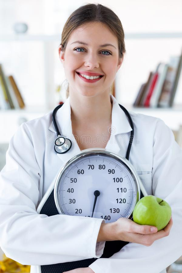 Young smiling female nutritionist holding weight scale and apple in the consultation. royalty free stock image
