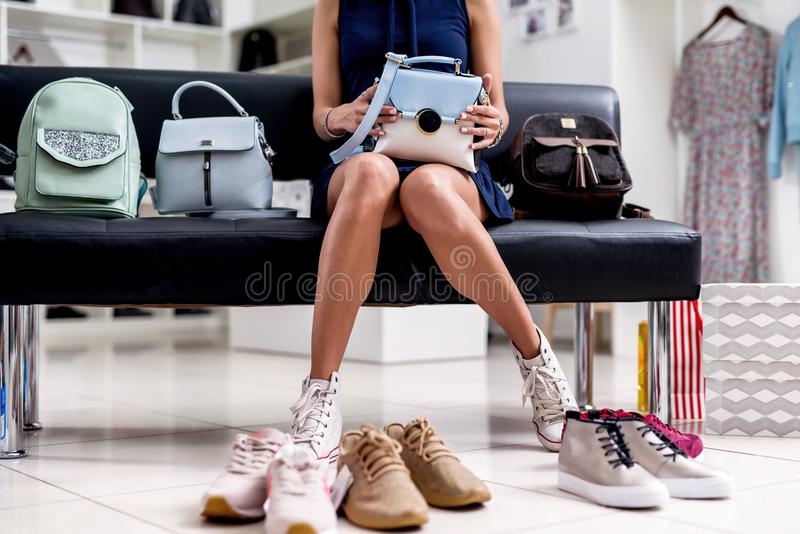 Portrait of young smiling female shopper sitting with a new handbag on her laps in accessories shop.  stock photo