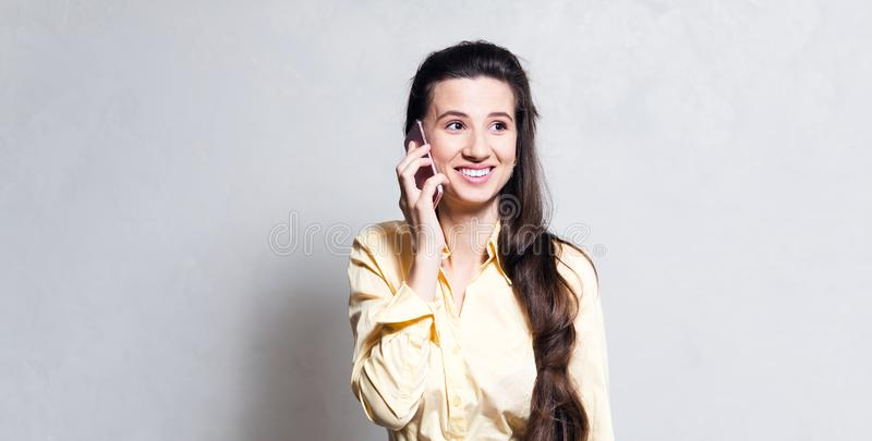 Portrait of young smiling girl talking on smartphone, dressed in yellow, over white background. royalty free stock images