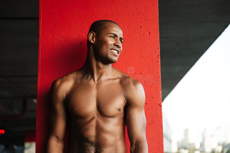 Portrait of a young smiling half naked african sportsman. Looking away while standing indoors stock images
