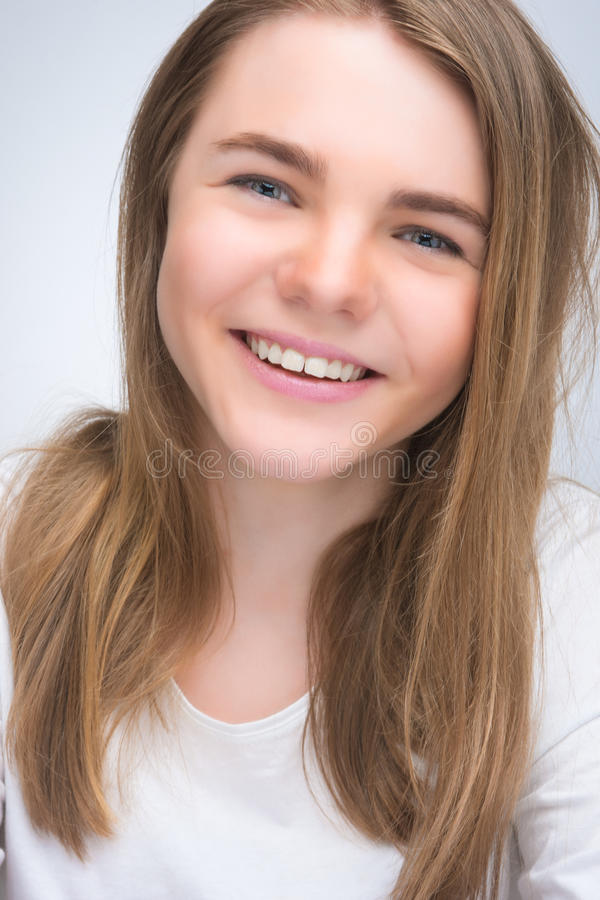 Portrait of young smiling happy teenager girl. Over gray background. vertical shot stock images