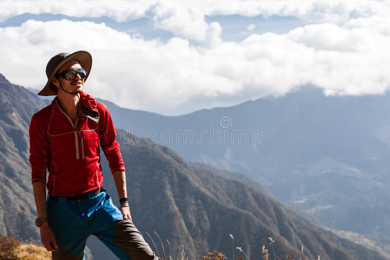 Portrait of young smiling Hiker in Mountains Cloud Cover. Portrait of young smiling Hiker in fedora Hat with Mountains and Cloud Cover on Background stock photos