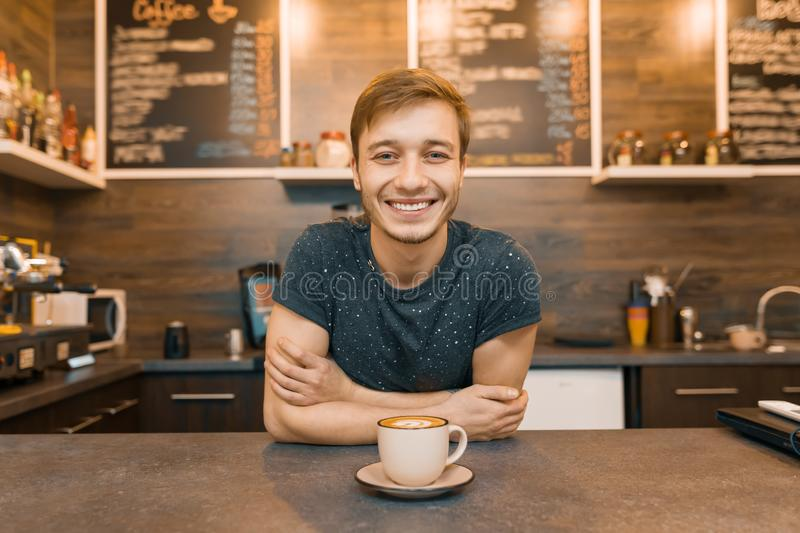 Portrait of young smiling male barista with prepared drink with arms crossed standing behind cafe counter. Coffee shop business co royalty free stock image