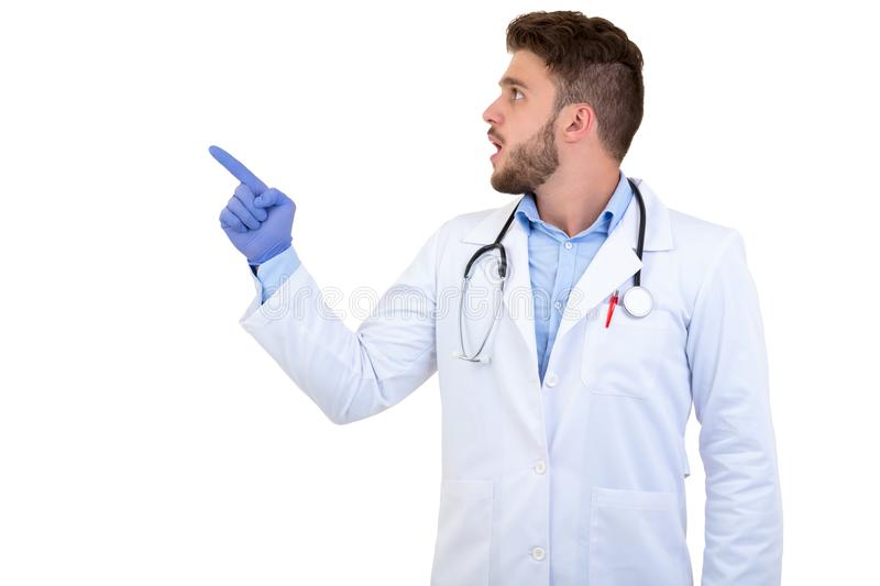 Portrait of a Young smiling male doctor pointing finger away isolated on a white background stock photography