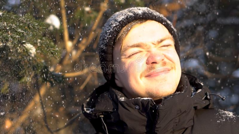 Portrait of young, smiling man with moustache enjoying snowfall in winter forest, squinting his eyes from the bright sun stock photos