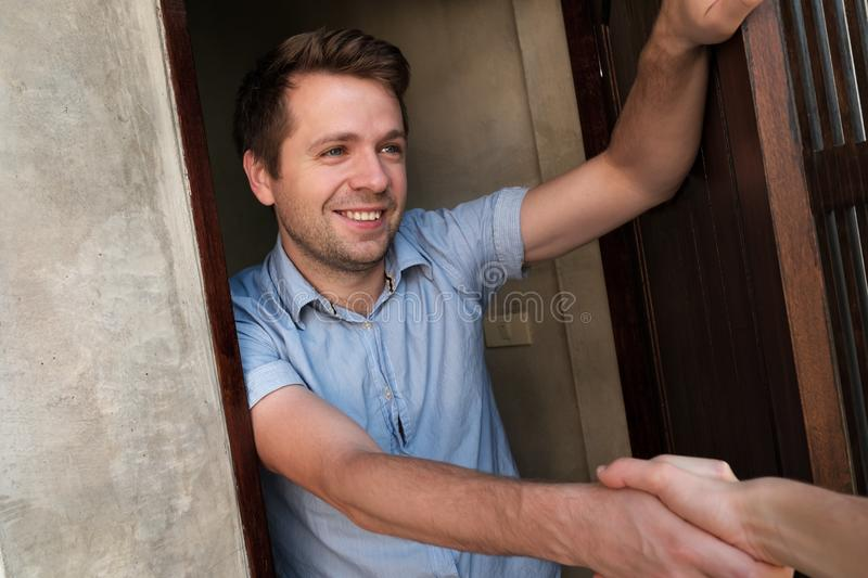 Portrait of young smiling man opening the door to his friend and welcoming him shaking hand stock image