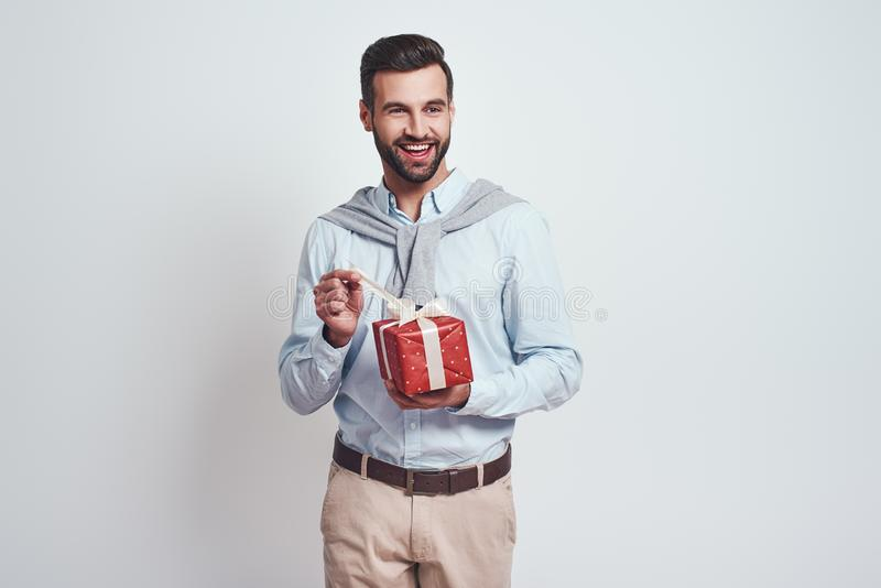 Portrait of a young smiling man opening gift box and looking at camera over grey background. Close-up image stock image