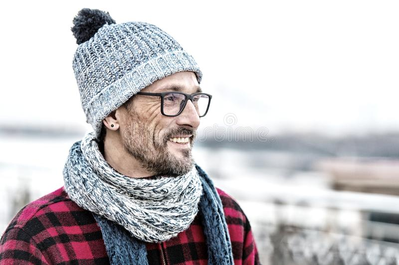 Portrait of young smiling man profile in glasses and warm knitted clothes for city man. stock photography