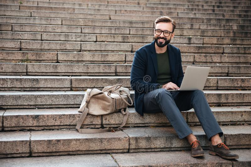 Portrait of young smiling man using laptop computer royalty free stock image