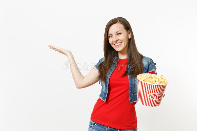 Portrait of young smiling pretty woman in casual clothes watching movie film, holding bucket of popcorn, pointing hand royalty free stock image