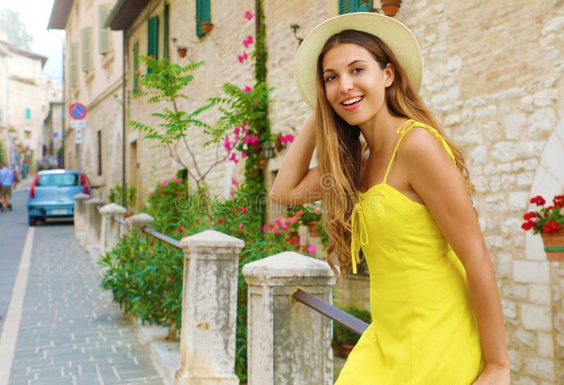 Portrait of young smiling tourist woman in long dress and straw hat in old Europe town royalty free stock images