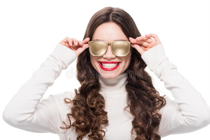 Portrait of young smiling woman with bright makeup wearing gold opaque sunglasses, stock photography