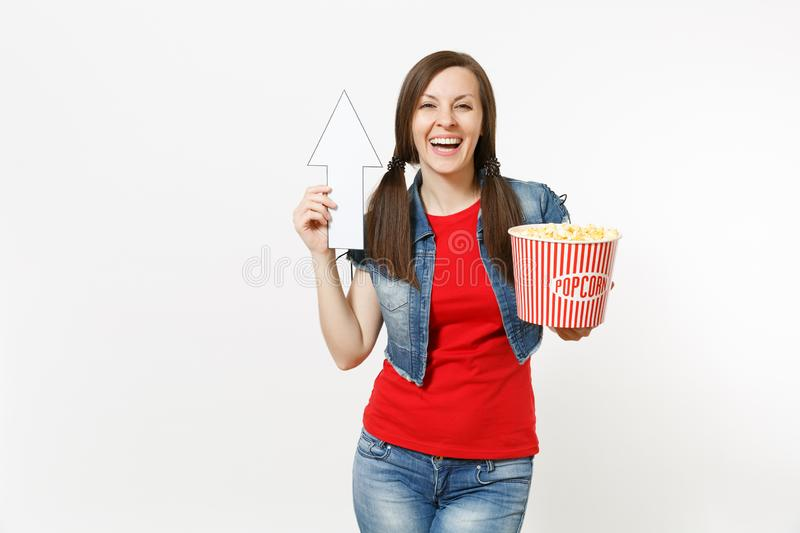 Portrait of young smiling woman in casual clothes watching movie film, holding bucket of popcorn, pointing white arrow. Up on copyspace isolated on white royalty free stock photo