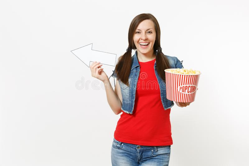 Portrait of young smiling woman in casual clothes watching movie film, holding bucket of popcorn, pointing white arrow. Aside on copyspace isolated on white stock photos