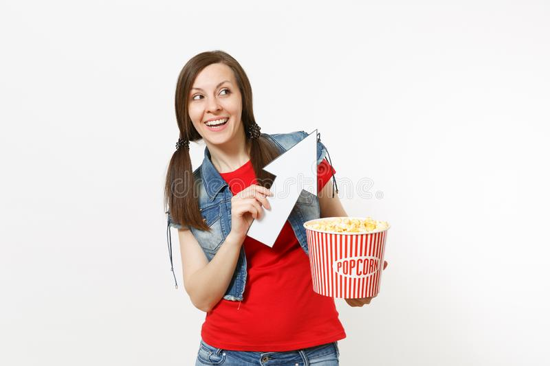 Portrait of young smiling woman in casual clothes watching movie film, holding bucket of popcorn, pointing white arrow. Up on copyspace isolated on white stock photos
