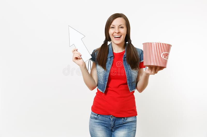 Portrait of young smiling woman in casual clothes watching movie film, holding bucket of popcorn, pointing white arrow. Up on copyspace isolated on white royalty free stock photography