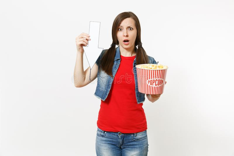 Portrait of young smiling woman in casual clothes watching movie film, holding bucket of popcorn, pointing white arrow. Up on copyspace isolated on white royalty free stock photos