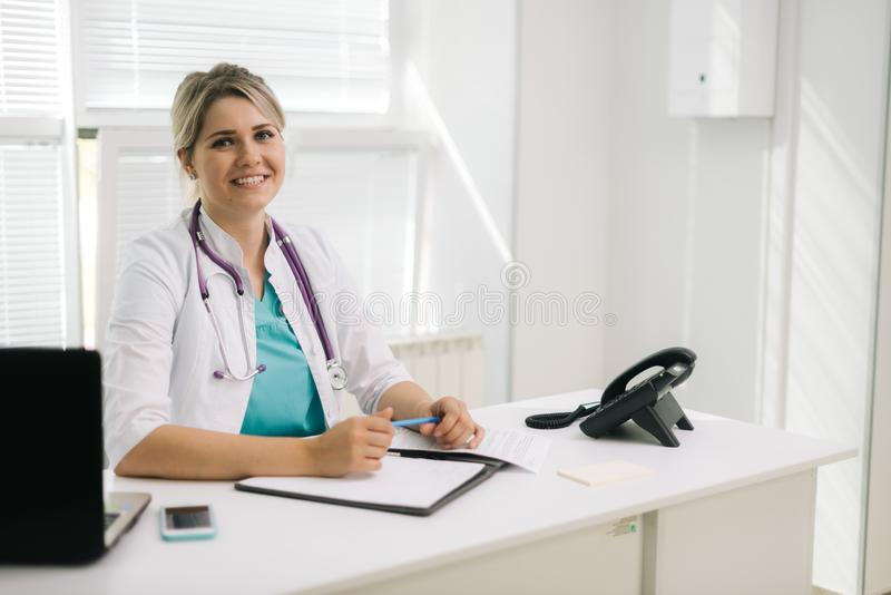 Portrait of young smiling woman doctor in office with laptop taking patient royalty free stock photo