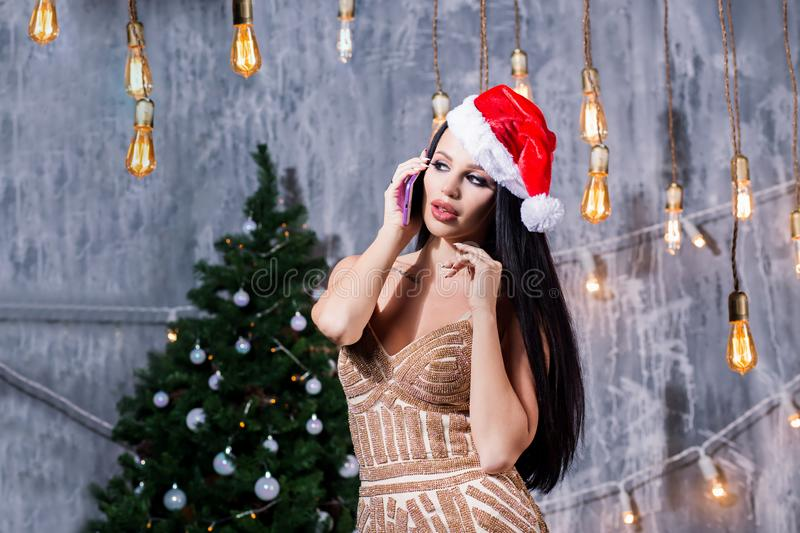 Portrait of a young smiling woman doing online shopping before christmas. New Years is soon. Holidays, New Year, celebration and people concept stock images