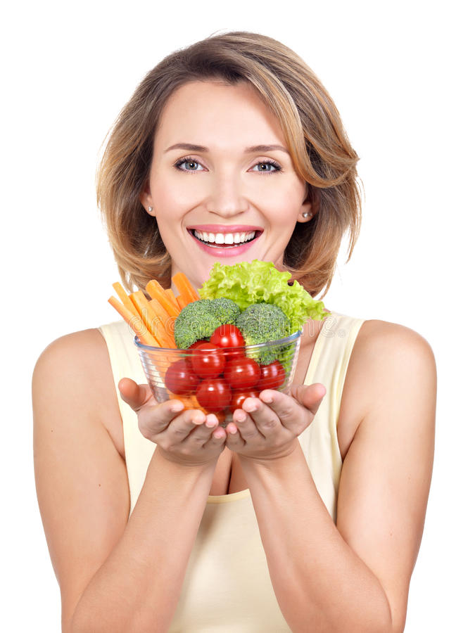 Portrait of a young smiling woman with a plate of vegetables. stock image