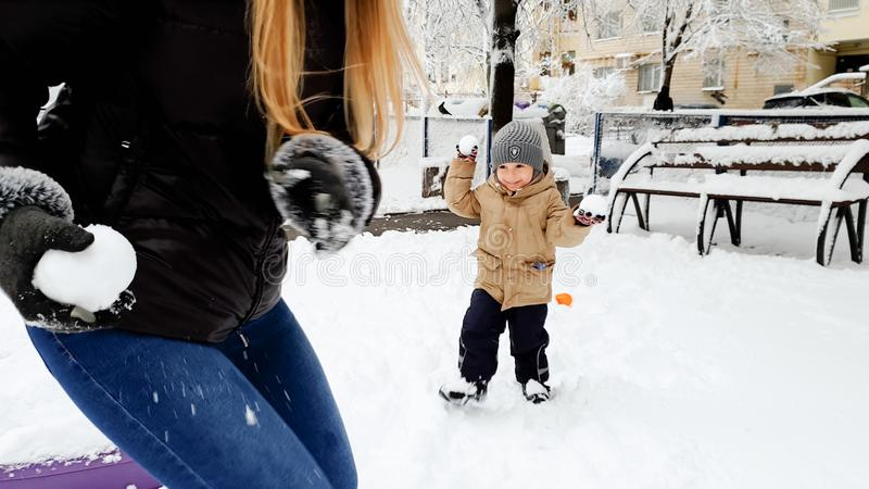 Close up portrait of young smiling woman playind in snow balls with her cute son in jacket and hat on the playground in stock photos
