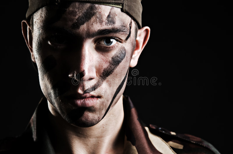 Portrait of young soldier in camouflage. Against black background stock photo