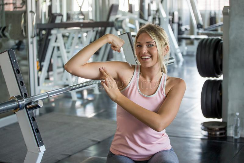 portrait of young sport woman in sportswear posing strong showing her biceps muscular arms in fitness gym . ,workout ,training stock photo